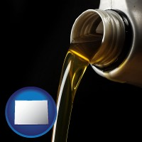 colorado pouring motor oil, on a black background